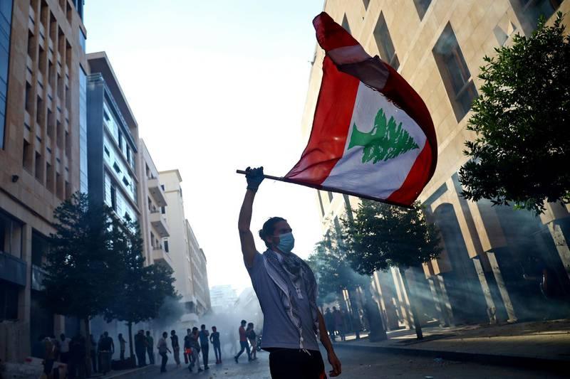 A demonstrator waves a Lebanese flag during anti-government protests that have been ignited by a massive explosion in Beirut, Lebanon August 10, 2020. REUTERS/Hannah McKay