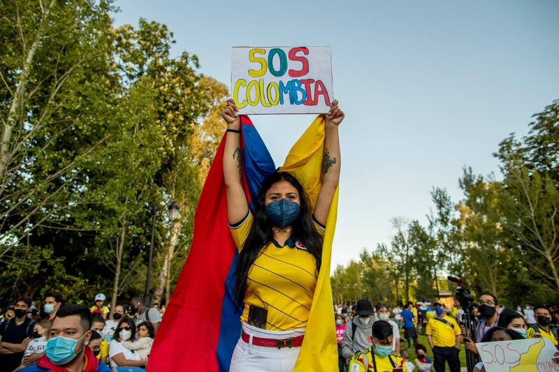 """A woman holds a banner reading: """"SOS Colombia"""" during a protest against the violence happening in Colombia against tax reform in Madrid, Spain, Thursday, May 6, 2021. The demonstration is in support of protests that began last week over a tax reform proposal that continue despite Colombia's President Ivan Duque's withdrawal of the tax plan. (AP Photo/Manu Fernandez)"""