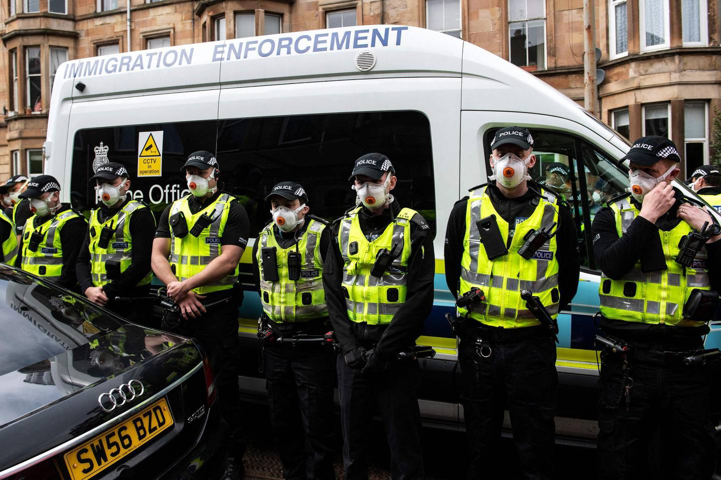 Protestors surround an Immigration Enforcement van to stop it from departing after individuals were detained in Glasgow on May 13, 2021. / AFP / Andy Buchanan