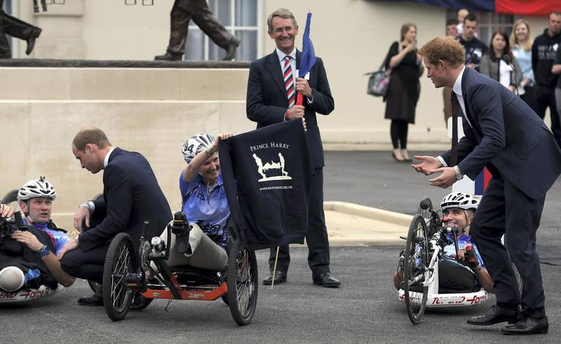 TIDWORTH, ENGLAND - MAY 20:  Prince Harry (R) receives a Help for Heroes hooded top from Corporal Claire Edwards (C) who is taking place in the 2013 Hero Ride, as he officially open the charity's Tedworth House recovery centre on May 20, 2013 in Tidworth, England. During their visit the two Royal Princes met with wounded veterans, serving personnel, and their families. Tedworth House in Wiltshire is one of four new units in England which will offer respite care and rehabilitation to injured and sick service personnel, veterans and their families.  (Photo by Matt Cardy/Getty Images)