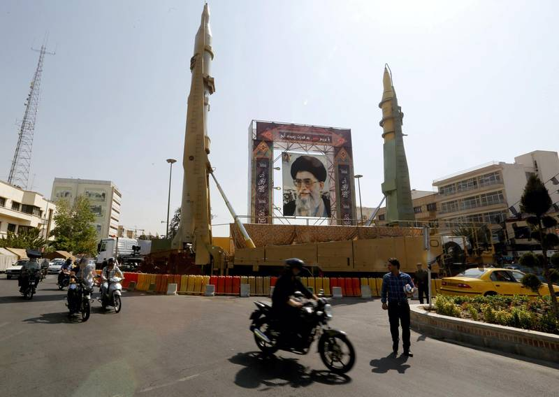 Iranians walk past Sejjil (L) and Qadr-H medium range ballistic missiles displayed next to a portrait of Iranian Supreme Leader Ayatollah Ali Khamenei on the occasion of the annual defence week which marks the anniversary of the 1980s Iran-Iraq war, on September 25, 2017, on Baharestan square in Tehran. / AFP PHOTO / ATTA KENARE