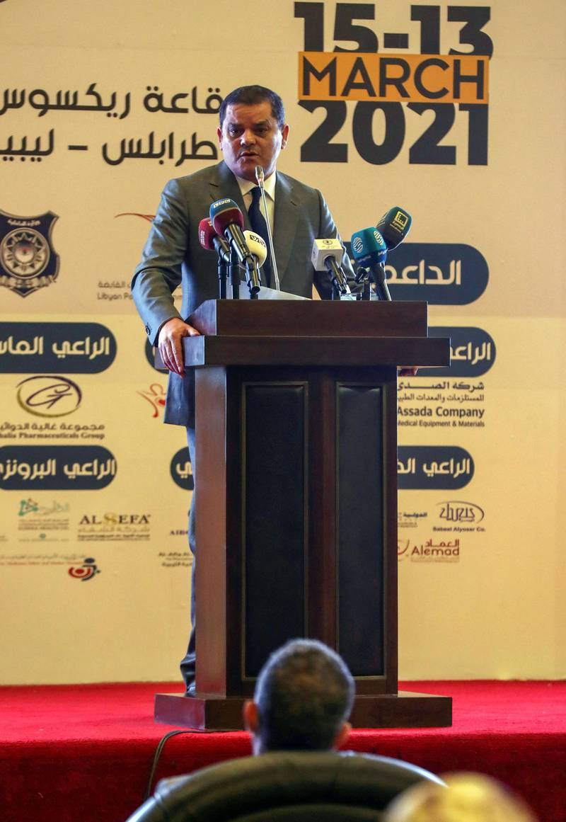 Libya's interim prime minister Abdul Hamid Dbeibah (L C) delivers a speech at a national conference on the COVID-19 pandemic, at a conference hall in the capital Tripoli, on March 13, 2021. / AFP / Mahmud TURKIA