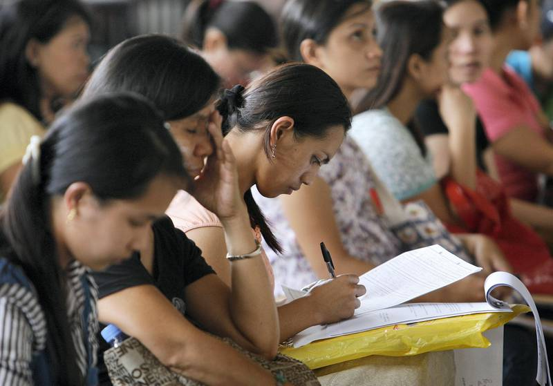 A woman fills an application form for a job posting in Kuwait during a job fair at the Philippine Overseas Employment Agency in Manila in this September 20, 2010 file photo. An average of more than 3,000 workers leave the country daily to work as professionals, nurses, doctors, domestic helpers, seafarers and labourers overseas. The Philippines, the world's fourth biggest recipient of remittances after India, Mexico and China, received more than $1.5 billion worth of remittances monthly from Filipinos working and living overseas. REUTERS/Cheryl Ravelo/Files (PHILIPPINES - Tags: EMPLOYMENT BUSINESS SOCIETY) - GM1E6BJ1JLH01