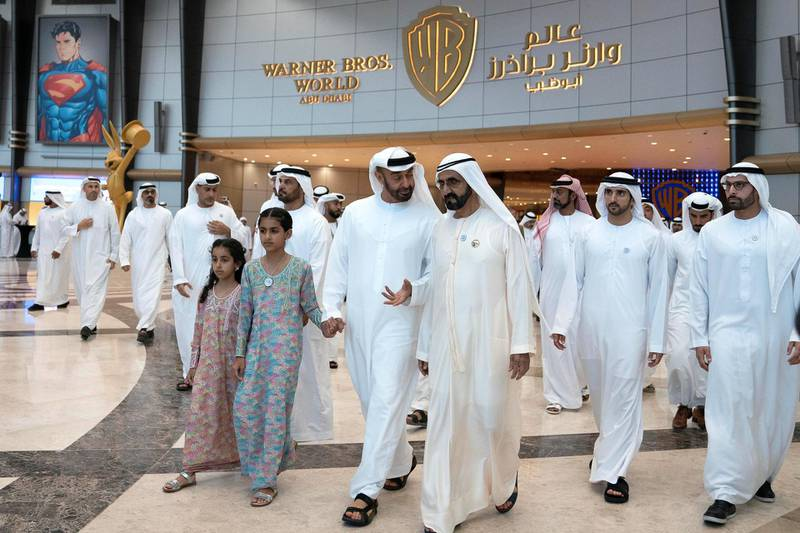 YAS ISLAND, ABU DHABI, UNITED ARAB EMIRATES - July 23, 2018: HH Sheikh Mohamed bin Zayed Al Nahyan, Crown Prince of Abu Dhabi and Deputy Supreme Commander of the UAE Armed Forces (2nd R) and HH Sheikh Mohamed bin Rashid Al Maktoum, Vice-President, Prime Minister of the UAE, Ruler of Dubai and Minister of Defence (R), attend the opening of Warner Bros World Abu Dhabi. Seen with HH Sheikha Salama bint Mohamed bin Hamad bin Tahnoon Al Nahyan (3rd R) and HH Sheikha Fatima bint Mohamed bin Hamad bin Tahnoon Al Nahyan (L). HE Mohamed Khalifa Al Mubarak, Chairman of the Department of Culture and Tourism and Abu Dhabi Executive Council Member (L) and HH Sheikh Hamdan bin Mohamed Al Maktoum, Crown Prince of Dubai (2nd L).   ( Eissa Al Hammadi for The Crown Prince Court ) ---