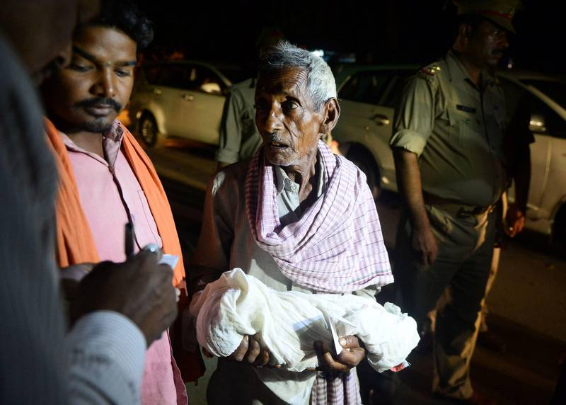 An Indian relative mourns as he carries a dead child outside the Baba Raghav Das Hospital in Gorakhpur, in the northern Indian state of Uttar Pradesh late August 12, 2017.  At least 60 children have died over five days at a government hospital in northern India that suffered oxygen shortages, officials said August 12 amid fears the toll could rise. Authorities said they have launched an inquiry but denied reports that a lack of oxygen had caused the deaths at the Baba Raghav Das Hospital in Gorakhpur district in Uttar Pradesh state, which is ruled by Prime Minister Narendra Modi's Bharatiya Janata Party. / AFP PHOTO / SANJAY KANOJIA