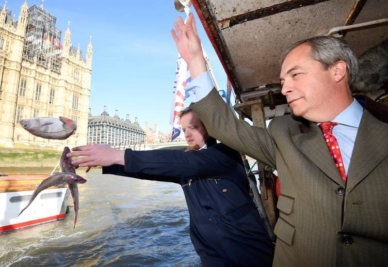 Brexit campaigner Nigel Farage and the founder of Fishing for Leave, Aaron Brown, symbolically dump fish into the River Thames next to the Houses of Parliament, to highlight what is says will be a detrimental effect a delay in leaving the Common Fisheries Policy will have on the British fishing industry, in central London, Britain March 21, 2018. REUTERS/Toby Melville