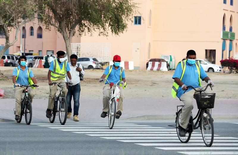 DUBAI, UNITED ARAB EMIRATES , April 18– 2020 :- Staff members of INAYA, facilities management company wearing protective face mask in International City in Dubai. Only two entrance are open for vehicles coming from Al Awir road before the Dragon Mart 1 and Manama Street to International City in Dubai.  Dubai is conducting 24 hours sterilisation programme across all areas and communities in the Emirate and told residents to stay at home. UAE government told residents to wear face mask and gloves all the times outside the home whether they are showing symptoms of Covid-19 or not.  (Pawan Singh / The National) For News/Online