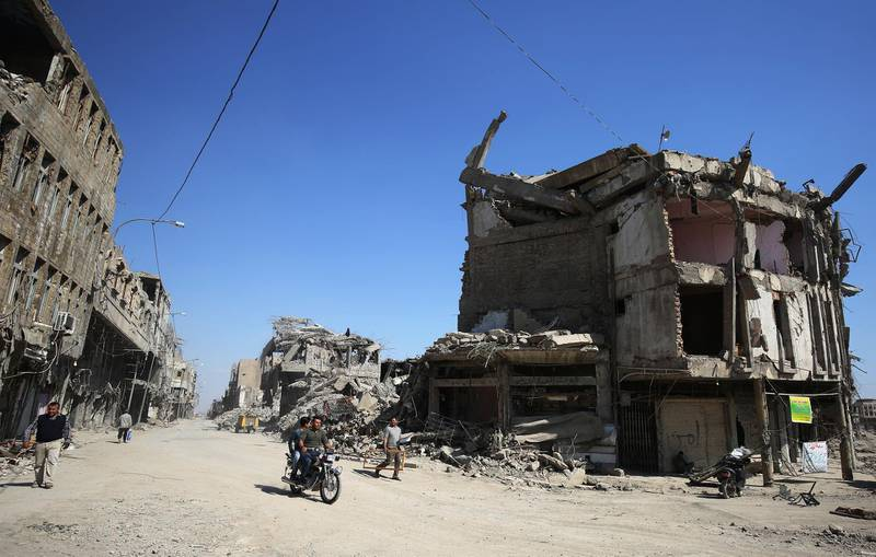 Iraqis pass destroyed buildings in the old city of Mosul on March 14, 2018, eight months after the Iraqi government forces retook the city from the control of the Islamic State (IS) group. / AFP PHOTO / AHMAD AL-RUBAYE