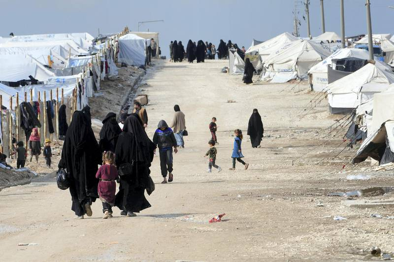 Veiled women, living in al-Hol camp which houses relatives of Islamic State (IS) group members, walk in the camp in al-Hasakeh governorate in northeastern Syria on March 28, 2019. (Photo by GIUSEPPE CACACE / AFP)