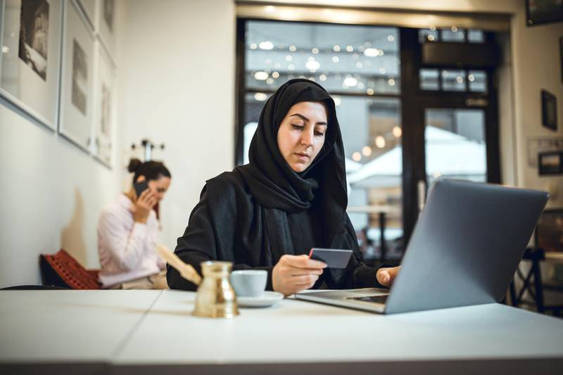 Muslim young woman shopping online at cafe using credit card