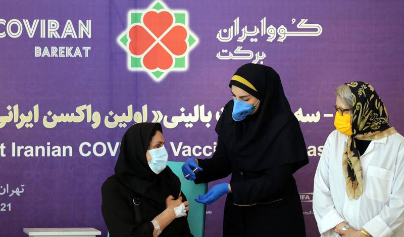 epa09075730 An Iranian health worker injects a dose of locally made COVID-19 vaccine 'COVIRAN Barekat' to Dr. Mehrnaz Rasoulinejad (L) at the beginning of second and third phases of the human test of the vaccine, in Tehran, Iran, 15 March 2021. Phases two and three of clinical trials of the locally-made covid-19 vaccine began on 15 March, after the first phase of human injection took place on 29 December. According to Mohammad Mokhber the head of COVIRAN Barekat vaccine department, the vaccine will be ready in summer for massive vaccination in Iran.  EPA-EFE/ABEDIN TAHERKENAREH