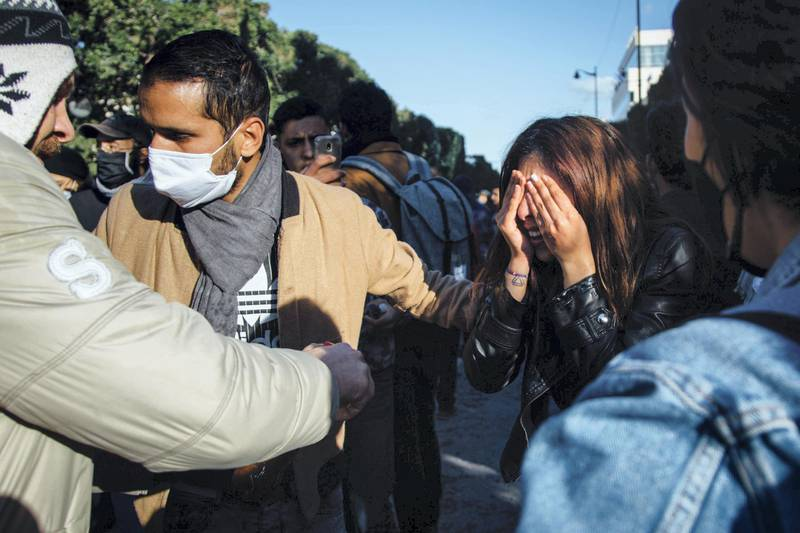A young protester washes her eyes with Coca-Cola after being pepper sprayed by police in downtown Tunis Tuesday. Erin Clare Brown / The National