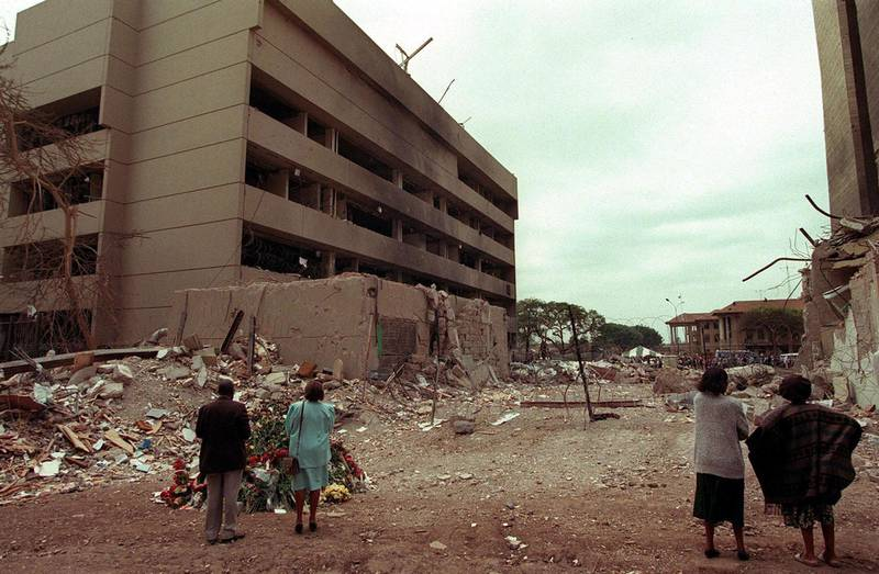 This August 1998 file picture shows Kenyan residents looking at the US embassy (L) days after the bomb blast that killed at least 280 kenyans and 12 american 07 August 1998. The jury in New York has begun deliberation in the bombings in Nairobi and Dar es Salaam and the verdict is expected in the next days. AFP PHOTO/FILES/ALEXANDER JOE (Photo by ALEXANDER JOE / AFP FILES / AFP)