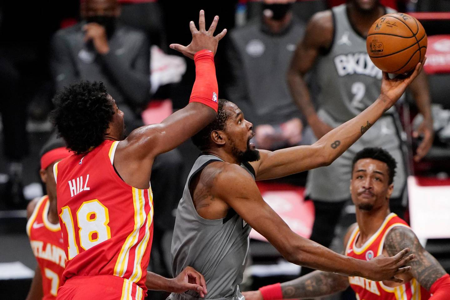 Brooklyn Nets forward Kevin Durant (7) tries to tip the ball in with Atlanta Hawks forwards John Collins (20) Solomon Hill (18) defending during the fourth quarter of an NBA basketball game, Wednesday, Dec. 30, 2020, in New York. (AP Photo/Kathy Willens)
