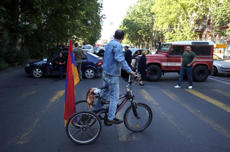 A supporters of the opposition lawmaker Nikol Pashinian rides a tricycle as he looks at people blocking a road in Yerevan on Wednesday, May 2, 2018. Pashinyan has urged his supporters to block roads, railway stations and airports on Wednesday after the governing Republican Party voted against his election as prime minister. (AP Photo/Thanassis Stavrakis)