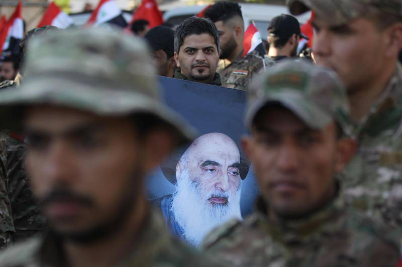 """A member of Hashed al-Shaabi holds a picture of Iraq's top Shiite cleric Grand Ayatollah Ali Sistani during the funeral procession of fellow comrades in Baghdad on December 31, 2019, who were killed on the weekend in US air strikes on a base in western Iraq near al-Qaim, on the border with Syria. Iraqi supporters of pro-Iran factions attacked the US embassy in Baghdad, breaching its outer wall and chanting """"Death to America!"""" in anger over weekend air strikes that killed two dozen fighters. It was the first time in years protesters have been able to reach the US embassy, which is sheltered behind a series of checkpoints in the high-security Green Zone.  / AFP / AHMAD AL-RUBAYE"""