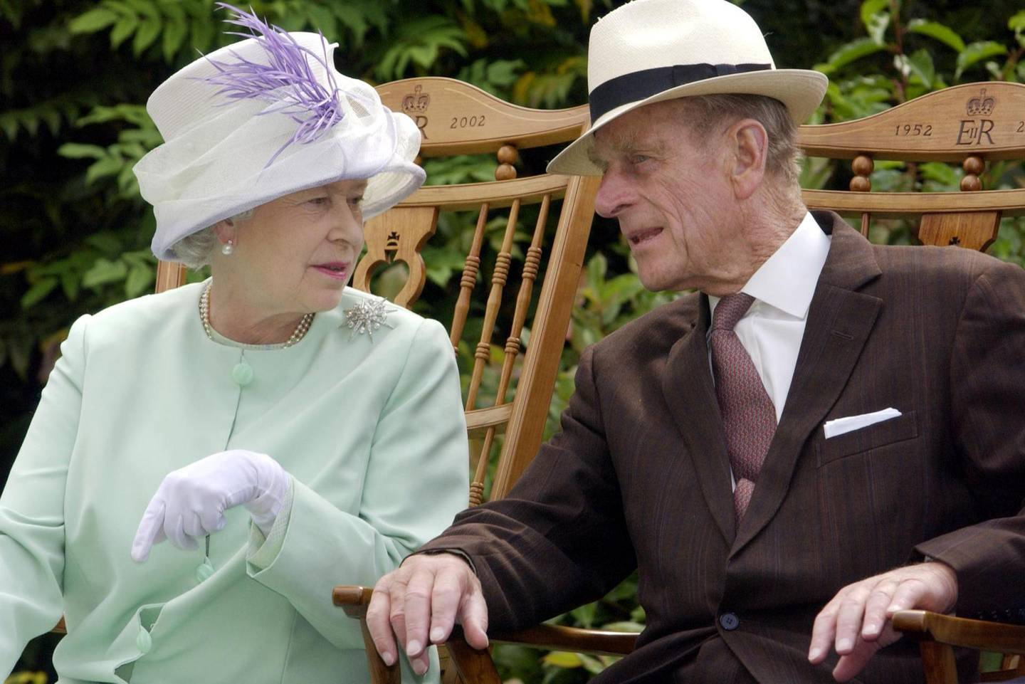 (FILES) In this file photo taken on July 17, 2002 Britain's Queen Elizabeth II (L) and Britain's Prince Philip, Duke of Edinburgh (R) chat while seated during a musical performance in the Abbey Gardens, Bury St Edmunds, during her Golden Jubilee visit to Suffolk, east of England. Prince Philip, the 98-year-old husband of Queen Elizabeth II, went into hospital on Friday, December 20, 2019 for precautionary treatment on a pre-existing condition, Buckingham Palace said. / AFP / Fiona HANSON