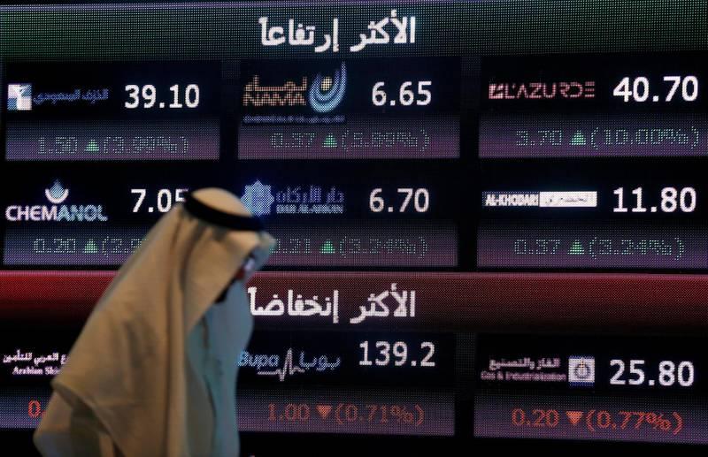FILE PHOTO: An investor walks past a screen displaying stock information at the Saudi Stock Exchange (Tadawul) in Riyadh, Saudi Arabia June 29, 2016. REUTERS/Faisal Al Nasser/File Photo