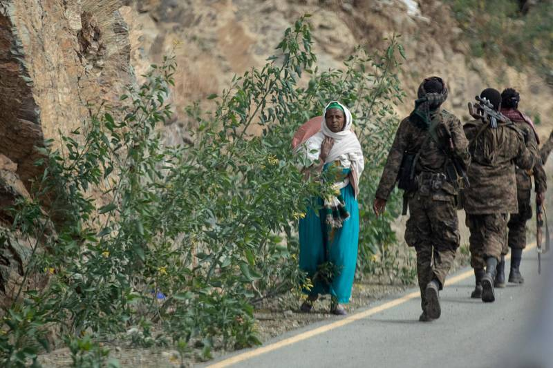 """FILE - In this Friday, May 7, 2021 file photo, a woman walks past Ethiopian government soldiers by the side of a road north of Mekele, in the Tigray region of northern Ethiopia. Ethiopia's government said in a statement carried by state media Monday, June 28, 2021, that it has """"positively accepted"""" a call for an immediate, unilateral cease-fire in its Tigray region after nearly eight months of deadly conflict. (AP Photo/Ben Curtis, File)"""