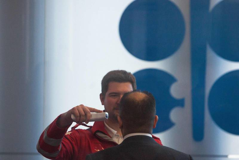A Red Cross medic measures the temperature of a participant of the 178th Organization of Petroleum Exporting Countries (OPEC) meeting in Vienna, Austria, on March 5, 2020.  Delegates from oil-producing countries started arrived in Vienna to discuss output cuts in a meeting overshadowed by worries over the new coronavirus -- both its affect on oil prices as well as a big gathering like OPEC. / AFP / ALEX HALADA