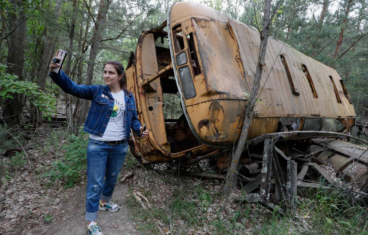 epaselect epa07633614 A visitor takes a selfie with an abandoned bus during a tour in Chernobyl, Ukraine, 07 June 2019. The miniseries Chernobyl (2019) made by HBO depicts the explosion`s aftermath, the vast clean-up operation and the subsequent inquiry. The success of a U.S. television miniseries examining the world`s worst nuclear accident has driven up the number of tourists wanting to see the plant and the ghostly abandoned town of Prypyat as local media report.  EPA/SERGEY DOLZHENKO