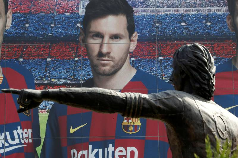 Soccer Football - Camp Nou, Barcelona, Spain - August 26, 2020   A statue of Johan Cruyff is seen infront of an image of Lionel Messi outside the Camp Nou after captain Lionel Messi told Barcelona he wishes to leave the club immediately, a source confirmed on Tuesday   REUTERS/Nacho Doce