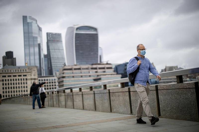 A man wearing a facemask as a precaution against the spread of the novel coronavirus walks across London Bridge with the offices of the City of London in Shard tower in the background on August 21, 2020. British government debt has exceeded £2.0 trillion for the first time following large state borrowing as the coronavirus pandemic pushed the UK economy deep into recession, official data showed on August 21. / AFP / Tolga Akmen