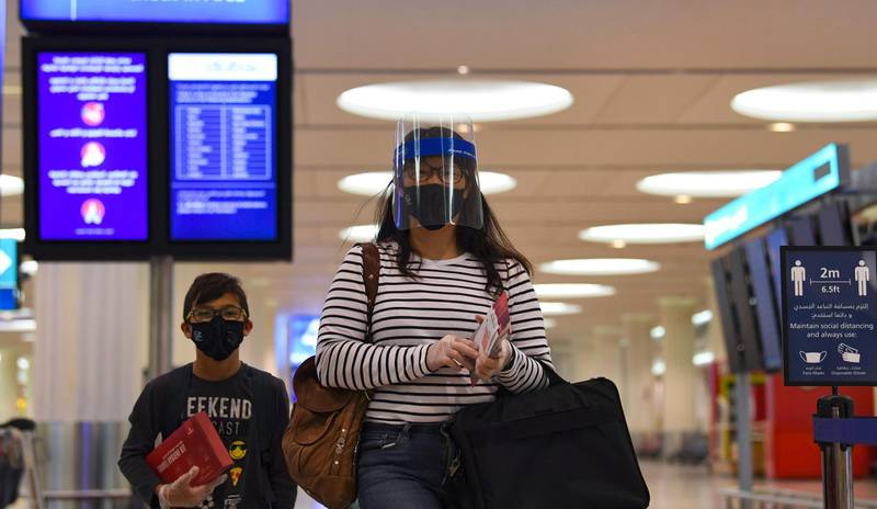 Passengers of an Emirates airlines flight, departing to the Australian city of Sydney, wear protective gear at Dubai International Airport on May 22, 2020, after the resumption of scheduled operations by the Emirati carrier, amid the ongoing novel coronavirus pandemic crisis.       / AFP / Karim SAHIB
