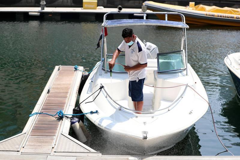 Dubai, United Arab Emirates - N/A. News. Coronavirus/Covid-19. A man at the marina hoses down a boat. Friday, September 11th, 2020. Dubai. Chris Whiteoak / The National
