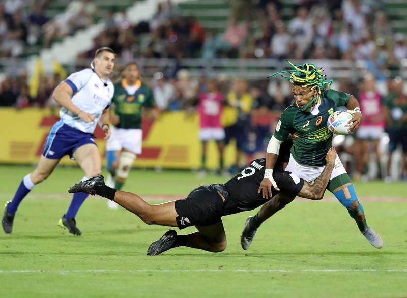 Dubai, United Arab Emirates - December 07, 2019: Rosko Specman of South Africa is tackled by Regan Ware of New Zealand during the game between New Zealand and South Africa in the mens final at the HSBC rugby sevens series 2020. Saturday, December 7th, 2019. The Sevens, Dubai. Chris Whiteoak / The National