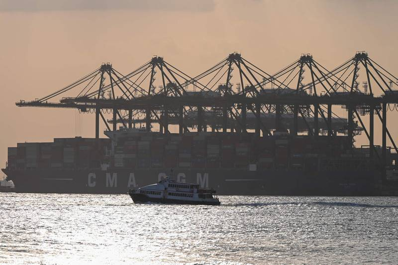 A boat sails past a vessel docked at Pasir Panjang container port at sunset in Singapore on January 18, 2021. / AFP / Roslan Rahman