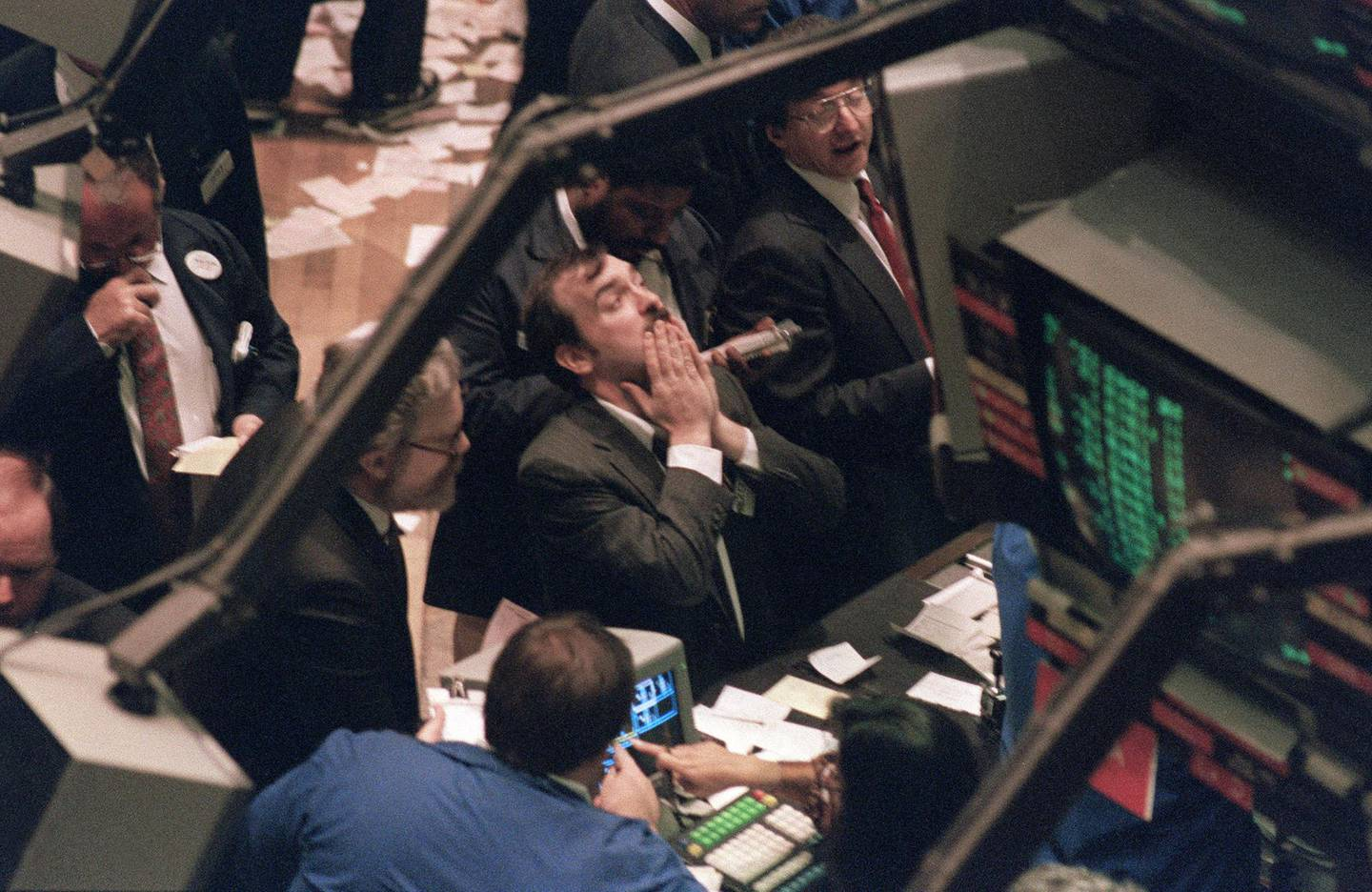 A trader (c) on the New York Stock Exchange looks at stock rates 19 October 1987 as stocks were devastated during one of the most frantic days in the exchange's history.  The Dow Jones index plummeted over 200 points in record trading. (Photo by MARIA BASTONE / AFP)