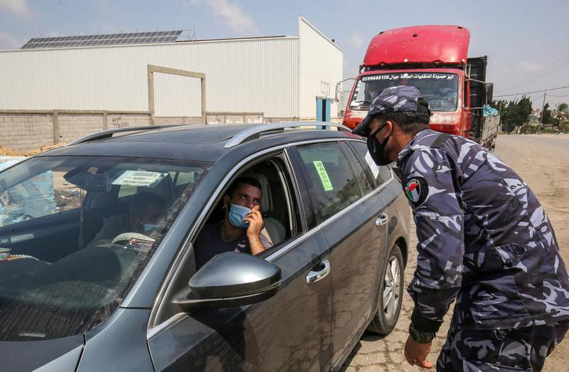 A Palestinian policeman speaks with a driver at a checkpoint in Rafah in the southern Gaza Strip on August 31, 2020, amid a lockdown due to increasing cases of COVID-19 infections. / AFP / SAID KHATIB