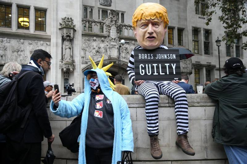 """LONDON, ENGLAND - SEPTEMBER 24: A person dressed as Boris Johnson holds a guilty sign as the Supreme Court building rules that the prorogation of Parliament was unlawful on September 24, 2019 in London, England. Britain's top court said that Prime Minster Boris Johnson acted unlawfully when he requested that the Queen prorogue parliament for more than a month, and that lawmakers should reconvene """"as soon as possible."""" (Photo by Hollie Adams/Getty Images)"""