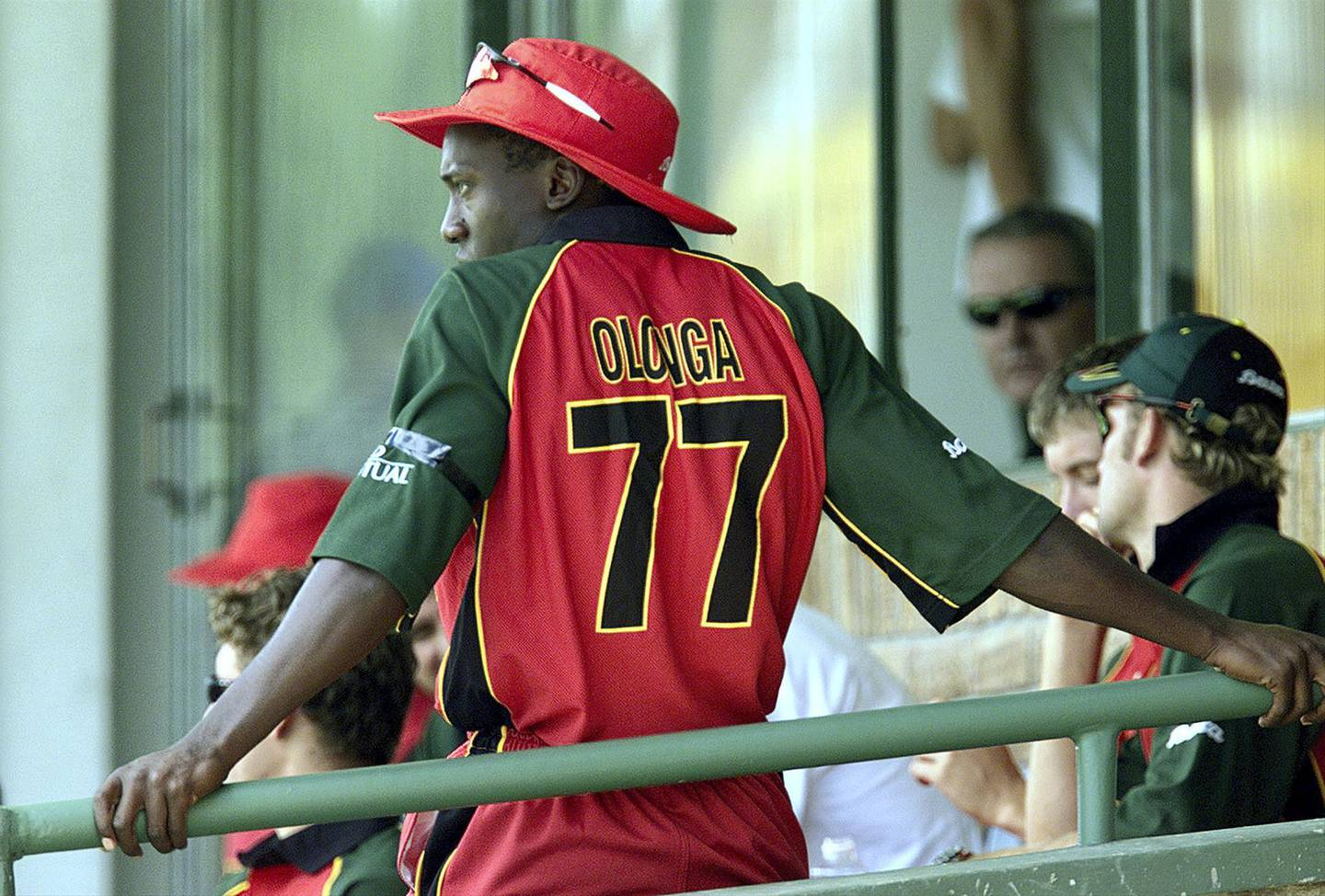 Zimbabwe bowler Henry Olonga wears a black armband in protest while in the players' enclosure during Zimbabwe's first Cricket World Cup match against Nambia at the Harare Sports Club February 10, 2003. Olonga and team mate Andy Flower, in a joint statement released just before Zimbabwe's Group A game, said they would wear black armbands during the event in an unprecedented attack on the running of the strife-torn country. REUTERS/Howard Burditt  HB/CRB - RP3DRIMSAWAA