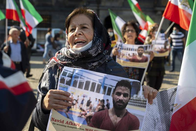 A woman holds a portrait of Iranian wrestler Navid Afkari during a demonstration on the Dam Square in Amsterdam, the Netherlands, on September 13, 2020, against its execution in the southern Iranian city of Shiraz and against the Iranian government. Iran said it executed wrestler Navid Afkari, 27, on September 12, 2020 at a prison in the southern city of Shiraz over the murder of a public sector worker during anti-government protests in August 2018. Reports published abroad say Afkari was condemned on the basis of confessions extracted under torture, prompting online campaigns of support for his release. - Netherlands OUT  / AFP / ANP / Evert Elzinga
