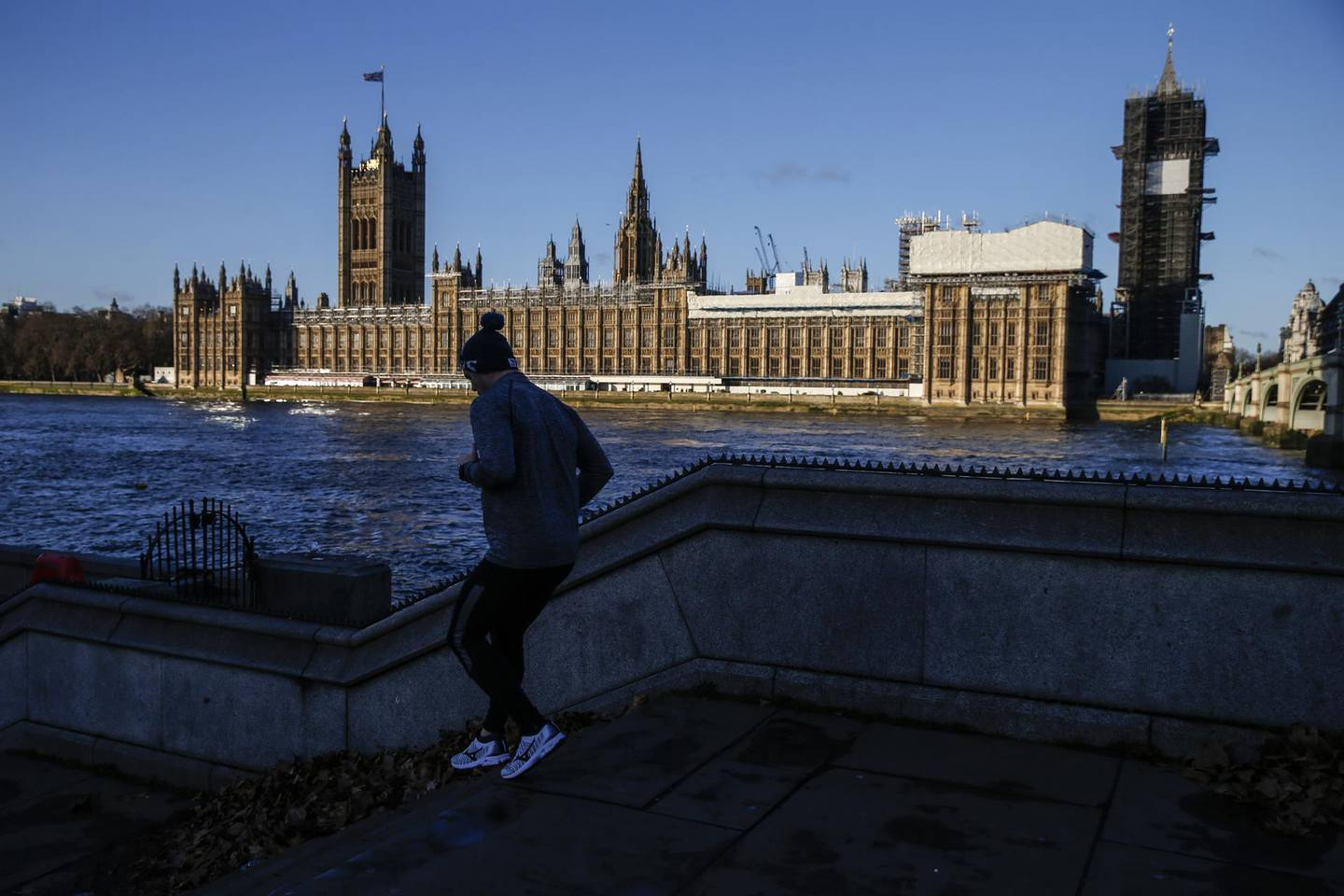 """A jogger runs along the Thames Path in view of the Houses of the Parliament in London, U.K., on Monday, Dec. 9, 2019. Prime MinisterBoris Johnsonsaid his Conservatives are putting their message across in """"every seat"""" as he goes into the final days of the U.K.'s general election campaign. Photographer: Hollie Adams/Bloomberg"""