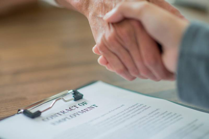 Two people are standing at a table, across from each other. Their hands grasp each others in a firm handshake. On the table sits a contract of employment. Getty Images