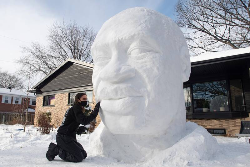 Timothee de Sandro puts the finishing touches on a snow sculpture of George Floyd in front of his house, Wednesday, Dec. 23, 2020 in Quebec City. De Sandro was shaken by the May, 2020 death of Floyd and wanted to pay tribute to him.  (Jacques Boissinot/The Canadian Press via AP)