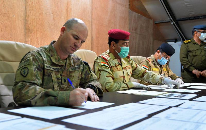 US army commander Jace Neuenschwander (L) and Iraq Nineveh Operations Commander Major General Noman Zawbai (C) and Iraq's Staff Major General Mohammad Fadhel Abbas sign documents during a handover ceremony at a base for the Combined Joint Task Force – Operation Inherent Resolve (CJTF-OIR), the US-led coalition against the Islamic State (IS) group, in Mosul in the northern Iraqi province of Nineveh during a handover ceremony to Iraqi forces on March 30, 2020. The US-led coalition is temporarily withdrawing training forces from Iraq as a protective measure against the novel coronavirus, a senior official in the alliance said on Thursday.  / AFP / Zaid AL-OBEIDI