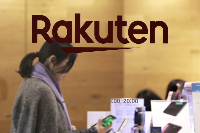 The Rakuten Inc. logo is displayed on a glass door while a customer looks at a smartphone inside the company's cafe in Tokyo, Japan, on Monday, Jan. 28, 2019. Rakuten's chief executive officer Hiroshi Mikitani says the company is aiming to lower prices in Japan's wireless market. Photographer: Kiyoshi Ota/Bloomberg