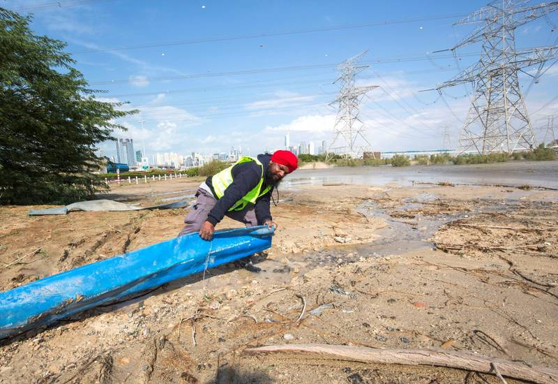 Dubai, United Arab Emirates - A municipal worker draining the flood off the street into this water holding area at a road closed to Batuta and Discover Gardens streets.  Ruel Pableo for The National