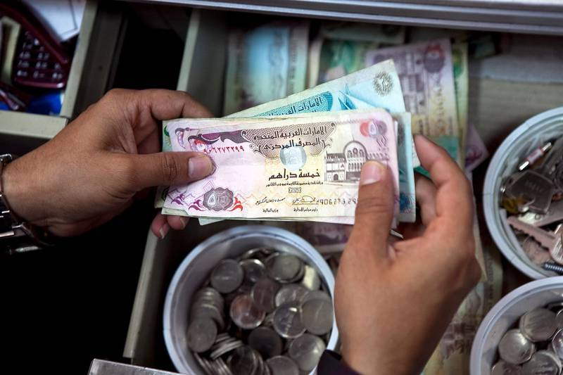 A store cashier receives payment from a customer on Tuesday, Nov. 8, 2011, at a local convenience store in Abu Dhabi. (Silvia Razgova/The National) currency dirham dirhams