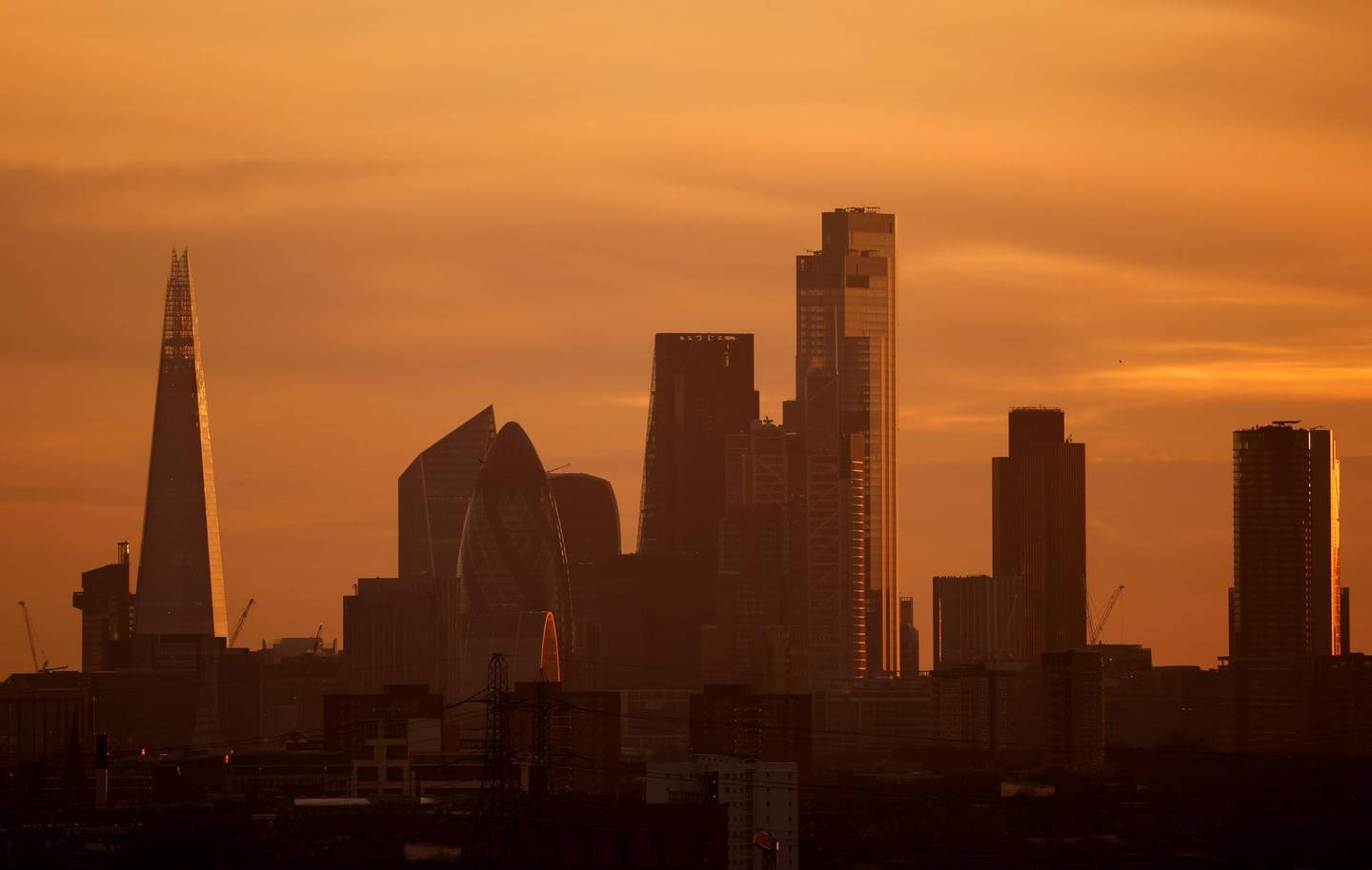 The skyscrapers and office buildings in the City of London, including The Shard (L), are bathed in yellow light during the autumn sunset on November 24, 2020. Britain's government, seeking to support the pandemic-ravaged economy and the nation's post-Brexit future, on Wednesday unveils its eagerly-awaited spending plans. Finance minister Rishi Sunak will deliver his spending review to parliament, one week before England ends a month of restrictions aimed at cutting a second wave of infections.  / AFP / Tolga Akmen