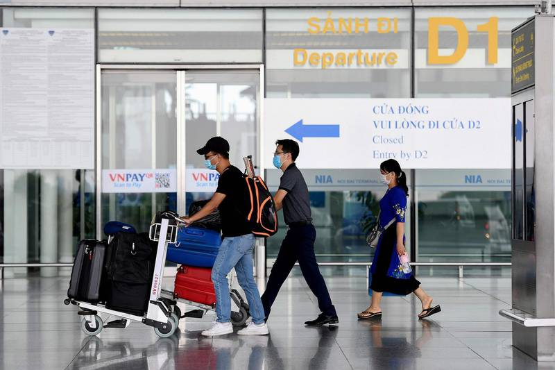 Passengers walk with their luggage at the departure terminal at Noi Bai International Airport in Hanoi on September 16, 2020. Vietnam said September 16 it will resume international commercial flights to and from six Asian destinations, months after a suspension due to the COVID-19 coronavirus. / AFP / Nhac NGUYEN