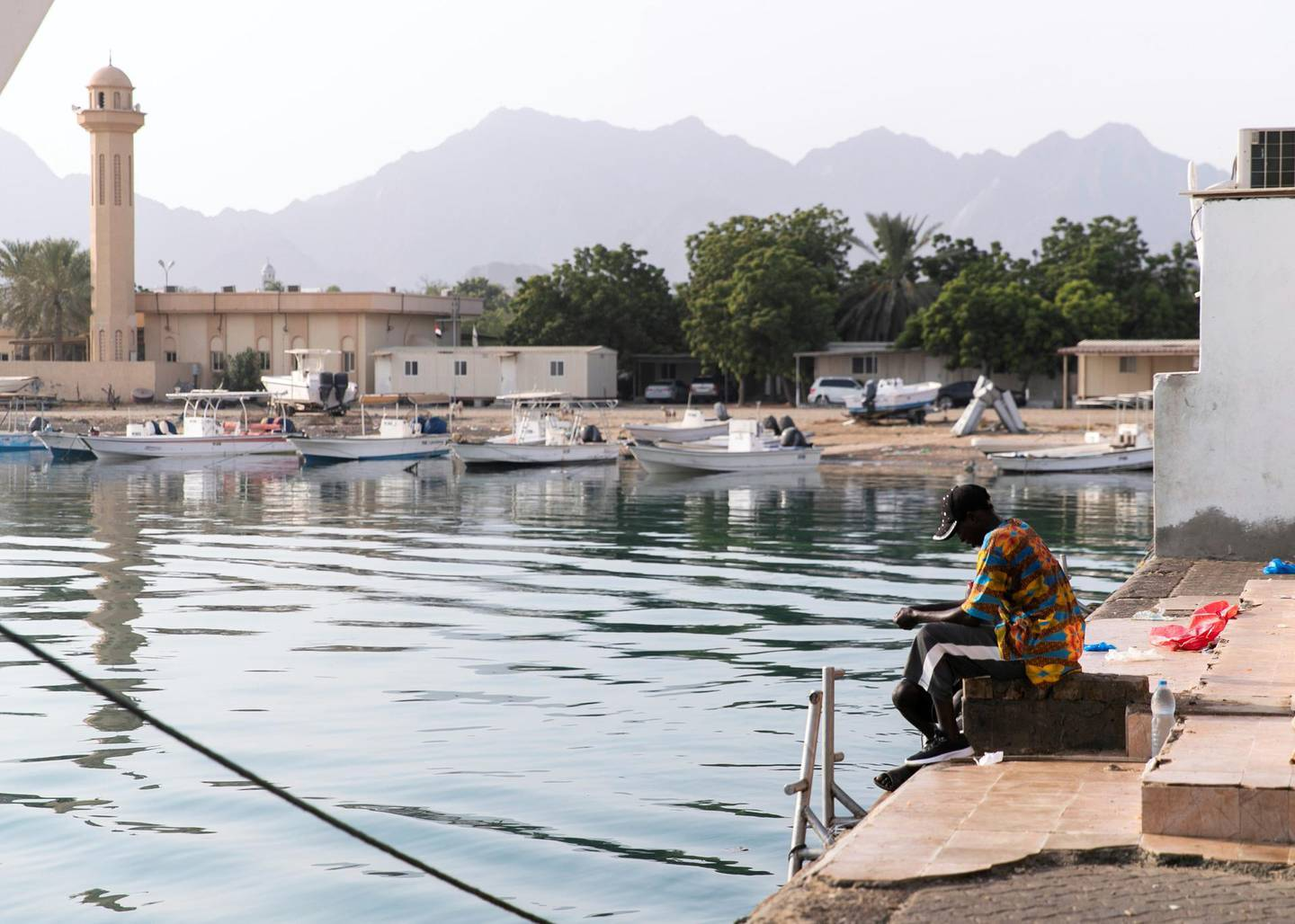 FUJAIRAH, UNITED ARAB EMIRATES. 3 AUGUST 2020. Two men fish in Dibba Al Fujairah's port.The UAE is calling on more volunteer divers to help restore and replant coral reefs in the open waters of Fujairah.Over the next five days, teams of volunteers will take fresh coral from Dibba Fujairah Port and replant it further out at sea, about 1km from Dibba Rock, a popular diving spot in the emirate.  The campaign is part of an initiative by the Ministry of Climate Change and Environment and Fujairah Adventure Centre to help sustain and grow marine life in UAE waters.(Photo: Reem Mohammed/The National)Reporter:Section: