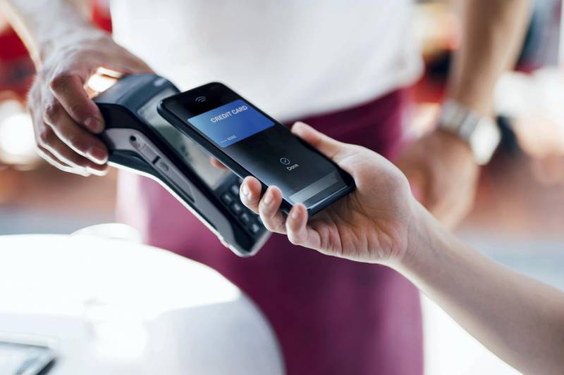 Close-up shot of a female hand using her smart phone to scan and pay for a bill at the restaurant during the day. Contactless payment, Technology Concept.