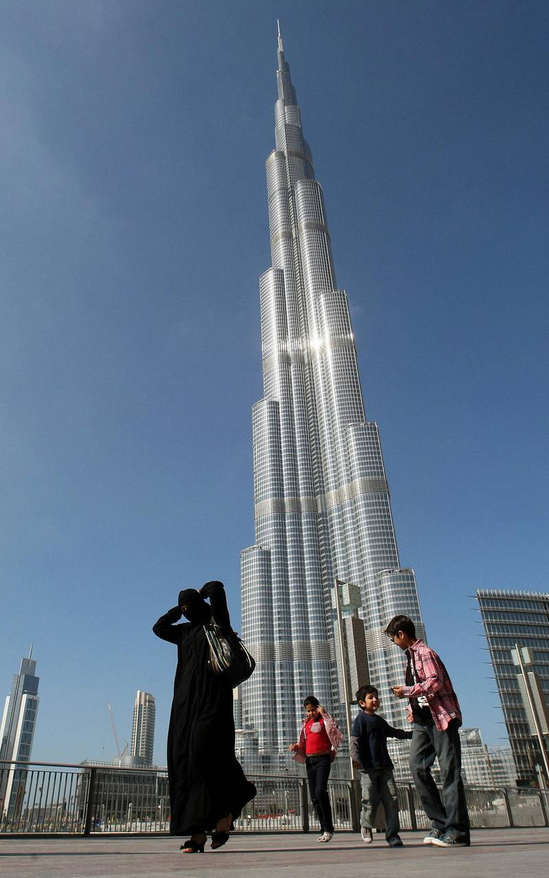 """(FILES) A picture taken on January 3, 2010 shows an Emirati woman and her children walking past Burj Khalifa, the world's tallest tower, in Dubai. Dubai's debt-laden group, Dubai World, said on May 20, 2010 it has reached an agreement """"in principle"""" with most of its bank lenders to restructure some 23.5 billion dollars in debt. AFP PHOTO/KARIM SAHIB (Photo by KARIM SAHIB / FILES / AFP)"""