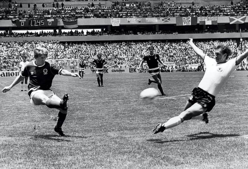Scotland's Gordon Strachan, left, scores his team's first goal during the Football World Cup match against West Germany in Queretaro, Mexico on June 8, 1986. West German player Norbert Eder attempts to stop the shot. West Germany defeated Scotland 2-1. (AP Photo/Staff/Kienzle)