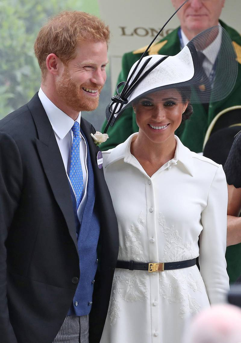 Britain's Prince Harry, Duke of Sussex, (L) and Britain's Meghan, Duchess of Sussex react after presenting the trophy for the St James's Palace Stakes race on day one of the Royal Ascot horse racing meet, in Ascot, west of London, on June 19, 2018. - The five-day meeting is one of the highlights of the horse racing calendar. Horse racing has been held at the famous Berkshire course since 1711 and tradition is a hallmark of the meeting. Top hats and tails remain compulsory in parts of the course while a daily procession of horse-drawn carriages brings the Queen to the course. (Photo by Daniel LEAL-OLIVAS / AFP)